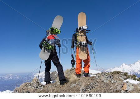 Snowboarders standing on top of a snowy mountain