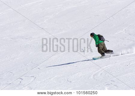 Snowboarder going down the slope at ski resort, extreme winter sport