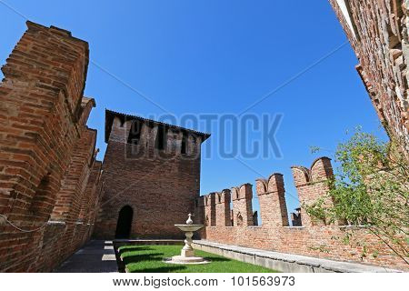 VERONA, ITALY - SEPTEMBER 2014 : A fountain and garden between fortified walls at Castle Fortress (Castelvecchio) in Verona, northern Italy on September 14, 2014.