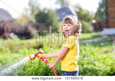 Happy girl pours water from a hose in garden