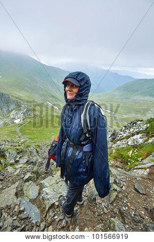 Woman In Raincoat On Mountain