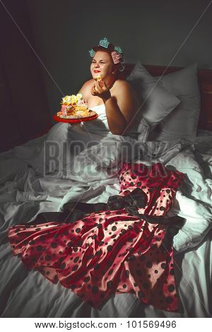 Portrait of beautiful plus size curly red hair young woman hiding under the blanket and eating sweet pastry in bed