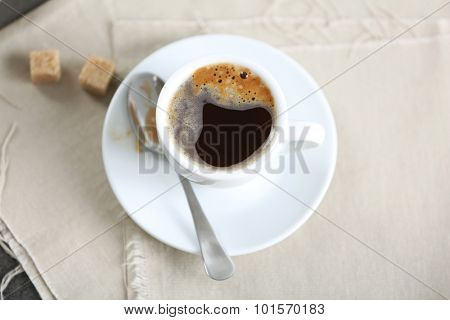 Cup of flavored coffee with lump sugar on table with napkin, closeup