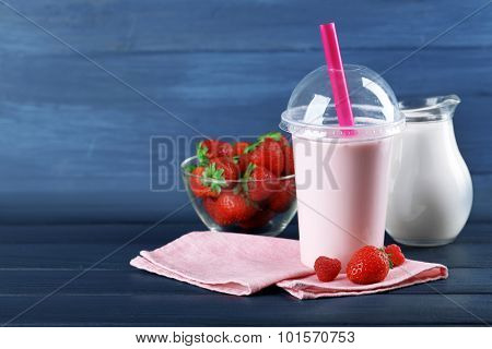 Plastic cup of milkshake on color wooden background