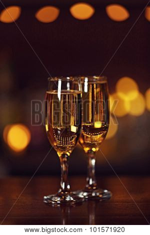 Two glasses of champagne, on bar counter, on blurred lights background