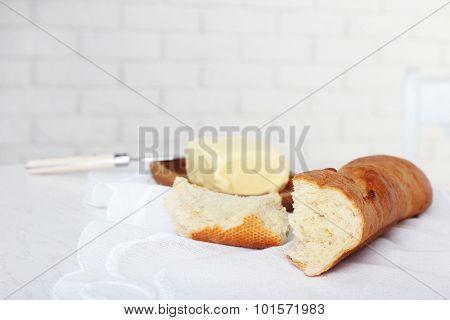 Broken baguette and butter on light background