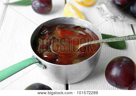 Tasty homemade plum jam in stew pot on wooden table, closeup
