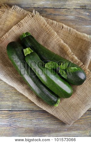 Fresh zucchini with basil on wooden table close up