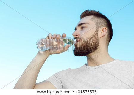Young man drinking water, hot day