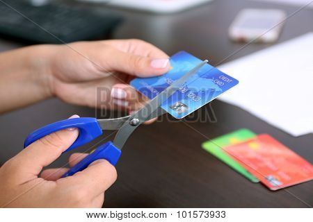 Woman's hands cutting bank card with scissors on wooden table background