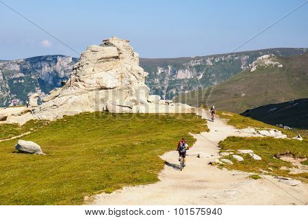 Unidentified biker climbs the hill in Bucegi Mountains in Romania