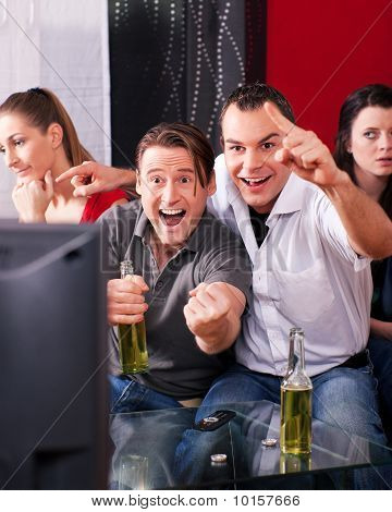 Friends watching exciting game at TV