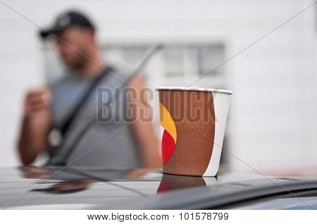 Coffee In A Paper Cup On The Roof Of The Car Closeup
