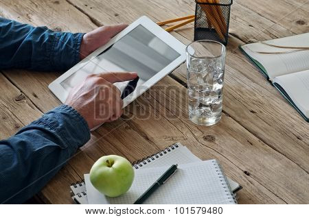 Man Working In The Office Using A Tablet Computer At A Wooden Table Closeup