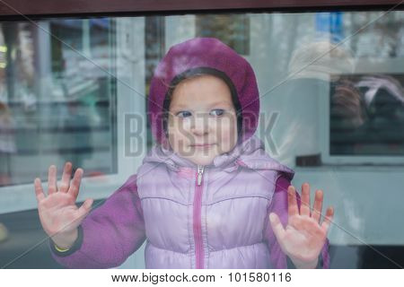 Portrait of toddler girl in warm hoodie through glass of display window