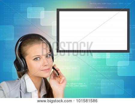 Businesslady in earphones looking at camera