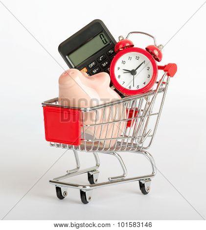 Piggy bank, calculator and clock in shopping cart