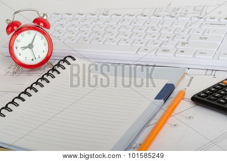 Exercise book and red  alarm clock