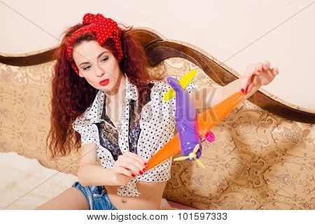 Closeup portrait of pretty young redhead woman playing on sofa