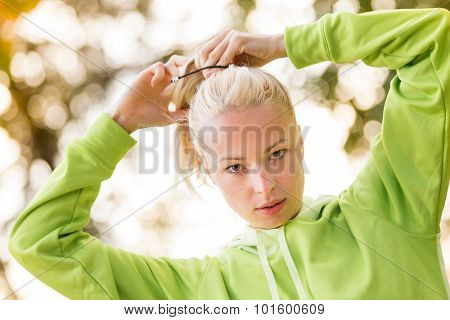 Confident sporty woman wearing fashionable green hoodie.