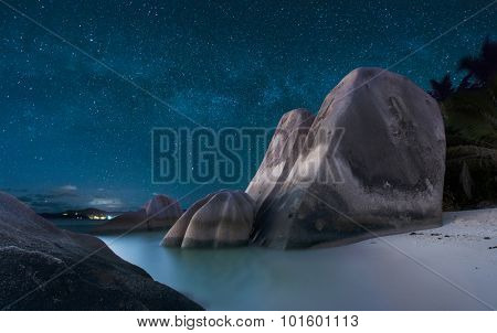 Stars with Milky Way over famous granite boulders at Anse Source d'Argent beach, La Digue island, Seychelles.