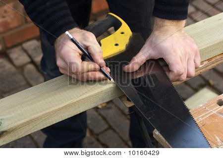 Carpenter Marking Out Wood With Saw