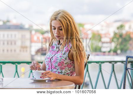 Blonde young woman drinks coffee in a cafe outdoors
