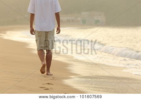 Man Walking And Leaving Footprints On The Sand Of A Beach