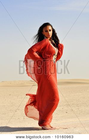 Beautiful Young Woman In Red Dress Posing On Arabic Desert.
