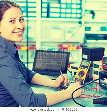 Woman with a tester and a printed circuit board. Colored photo