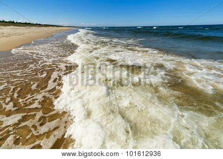 Baltic sea beach with frothed water near Gdansk, Poland.