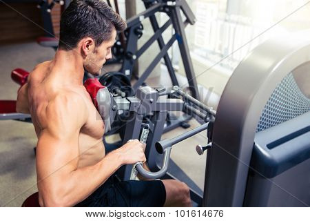 Portrait of a handsome man doing exercise on fitness machine in gym