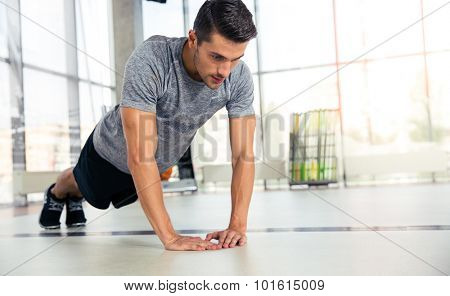 Portrait of a sports man doing push-ups in gym
