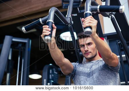 Portrait of a handsome bodybuilder doing exercise on fitness machine in gym
