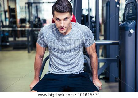 Portrait of a handsome sports man doing exercise on a fitness machine in gym
