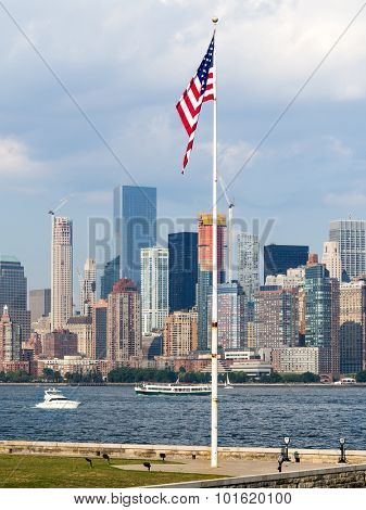 New York skyline with an american flag as seen from Ellis Island