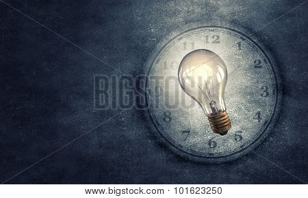 Conceptual image with light bulb and clock on dark background