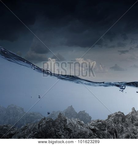 Underwater image of sea bottom and stormy sky