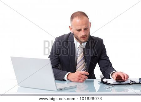 Elegant businessman sitting at desk over white background, having laptop, checking time on mobilephone.