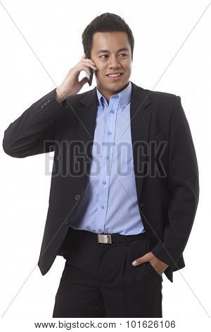 Businessman talking on mobilephone, looking away, standing with hand in pocket.