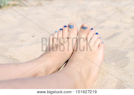 Woman Sandy Feet With Blue Nails Pedicure Relaxing On The Beach
