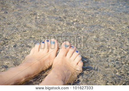 Woman Feet With Blue Pedicure Relaxing In Water On The Seashore