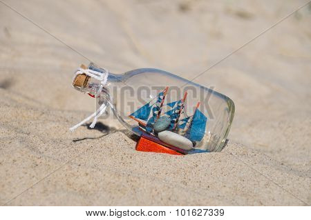 Small Ship In The Glass Bottle Lying In The Sand, Souvenir Concept
