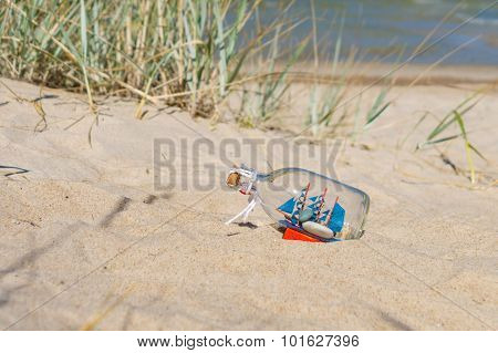 Small Ship In The Glass Bottle Lying On The Sandy Beach, Souvenir Concept
