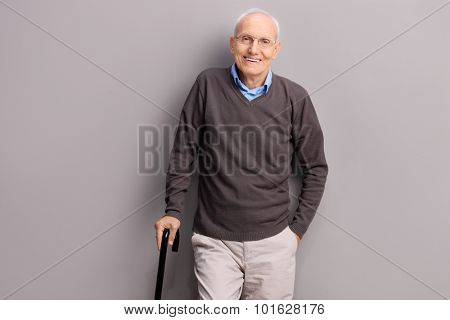 Senior gentleman holding a black cane and leaning against a gray wall