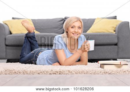 Blond woman lying on the floor in front of a gray sofa and holding a cup of coffee isolated on white background