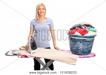 Blond woman posing behind an ironing board with a basket full of clothes on it isolated on white background