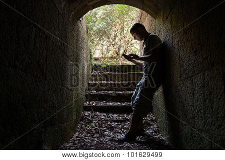 Young Man Works On A Smart-phone In Dark Tunnel