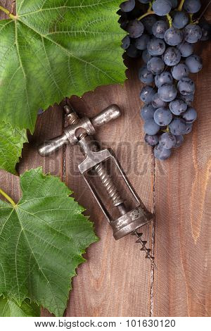 Red grape and vintage corkscrew on wooden table