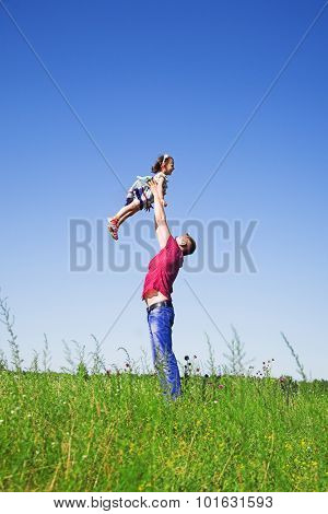 Happy family rest on the summer meadow, father fun throws up daughter in the air.